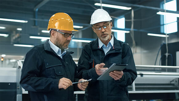two-engineers-in-hardhats-discuss-information-on-a-tablet-computer-picture-id838527388